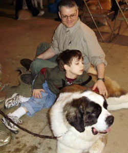 Saints for Safety, Security and Serenity trained Saint Bernard Penny to help an autistic boy, Nathan. Penny spends family time with Nathan and his father.